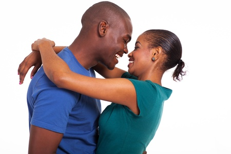 cheerful young african couple hugging isolated on white Фото со стока