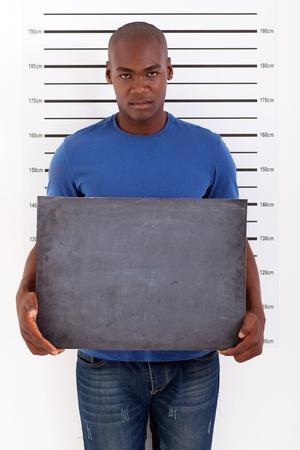 young african man holding a black board police mug shot photo