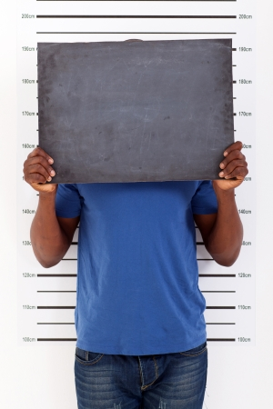 man in jail: funny african man police mug shot Stock Photo