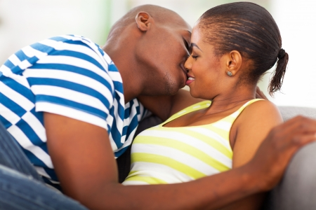 couple couch: close up portrait of young african couple kissing Stock Photo