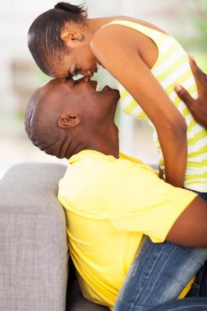 pareja apasionada: joven pareja african coqueteando en el sofá
