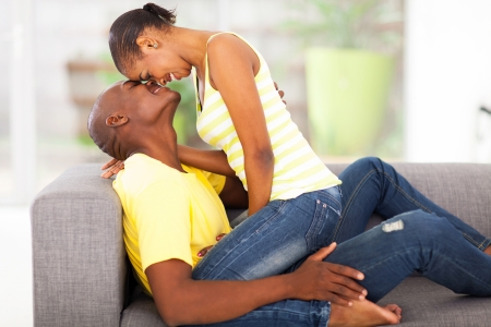 baiser amoureux: belle jeune femme africaine assis sur petit ami flirt
