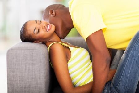 enamorados besandose: pareja joven afroamericano que se besan en el sof� Foto de archivo