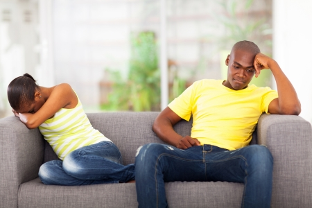 angry couple: young african couple having conflict sitting on the sofa