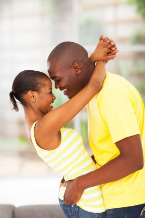 man woman hugging: passionate young african couple flirting and having fun