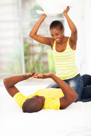 couple fight: playful young african couple pillow fight in bedroom Stock Photo