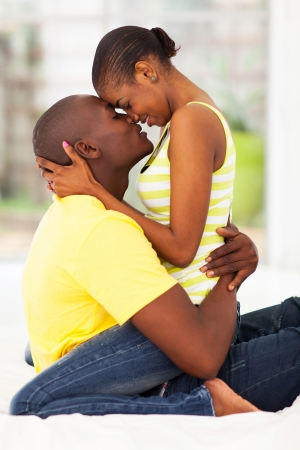 couples people: cute young african american couple kissing in bed