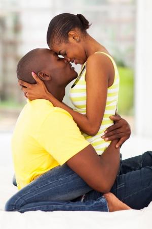 pareja en la cama: linda joven African American besando en la cama
