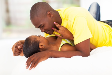passionate lovers: intimate young african couple in bed
