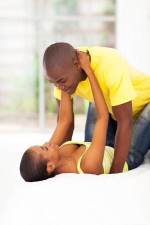 pareja apasionada: amantes de la joven pareja africana en la cama que se divierte Foto de archivo