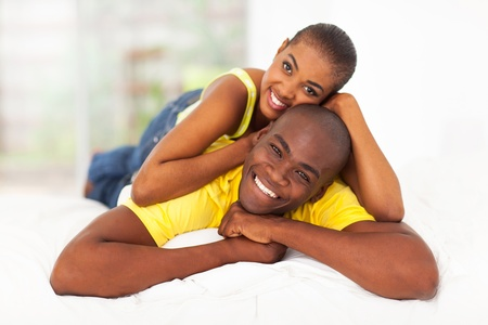 cheerful young black couple lying in bed