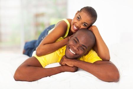 parejas felices: negro alegre pareja joven en la cama Foto de archivo