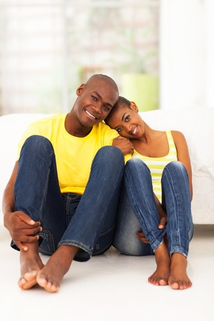 adult dating: cheerful young african couple sitting on the bedroom floor