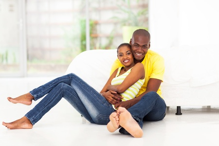 african american male: romantic african american couple sitting on bedroom floor