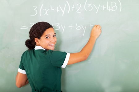 beautiful preteen girl: smiling female student student writing mathematics on the blackboard in classroom Stock Photo