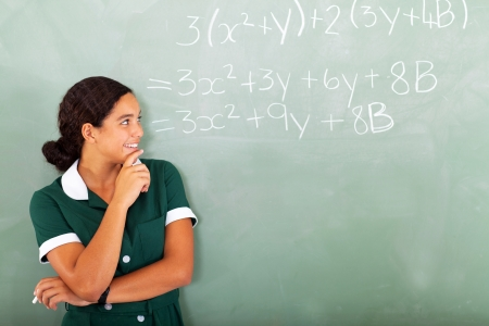 happy female high school student in classroom looking at  maths writing on the blackboard photo