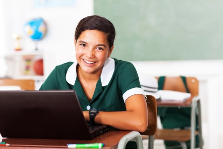 happy female middle school student using laptop in classroom