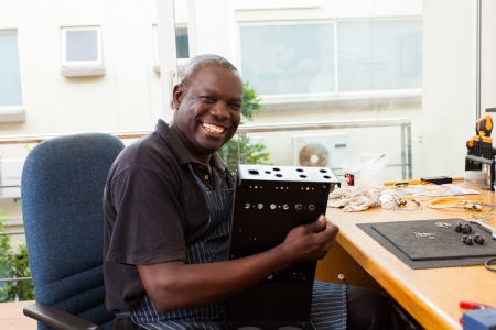 senior african man assembly electronic equipment in workshop photo