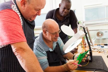 group of senior casual electrical technicians examining a circuit board photo