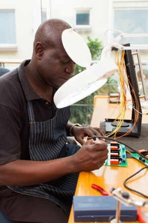 repair shop: senior african technician repairing a circuit board under electronic magnifying glass