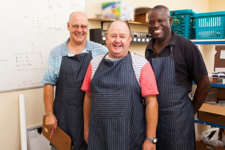 employers: happy senior small business owner and two employees in workshop Stock Photo