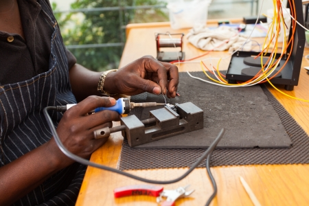senior african electrician using soldering iron repair a push button photo