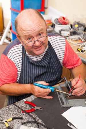 happy senior technician working with soldering iron in workshop photo