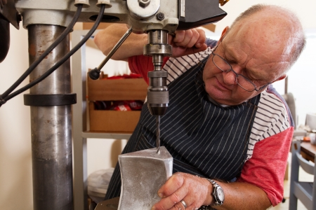 senior metal worker using industrial drilling machine in workshop Stock Photo - 19360997