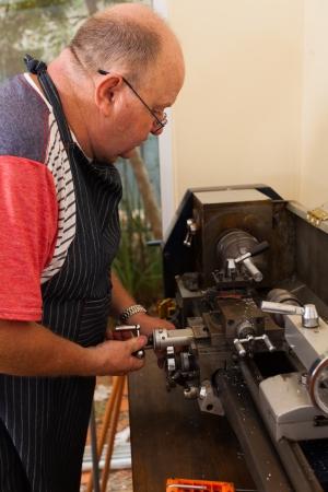 experienced operator: senior man using industrial lathe machine Stock Photo