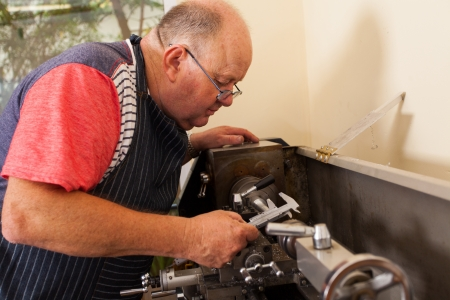 experienced operator: senior man operating lathe machine in workshop
