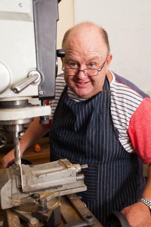 happy senior man operating drill press in workshop Stock Photo - 19360966