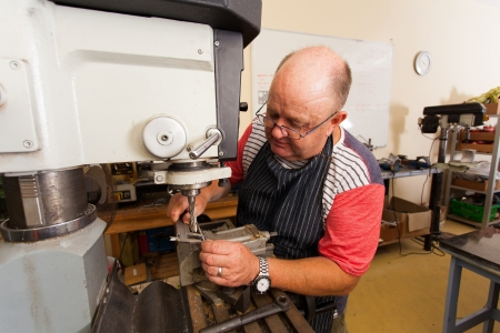 senior male artisan working on industrial drilling machine in workshop Stock Photo - 19360971