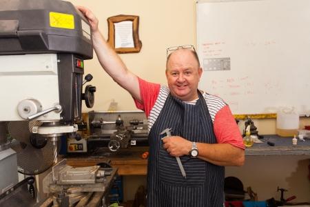 happy senior machinist in workshop  photo