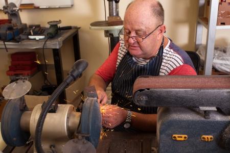 senior man using grinding machine in workshop photo