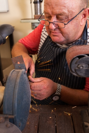 senior repairman using grinding machine in workshop photo