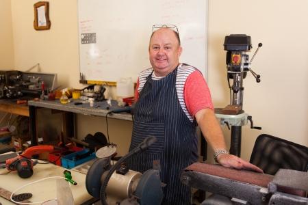 happy senior machinist portrait in workshop photo