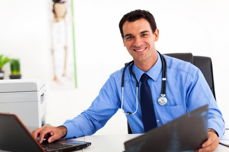 healthcare office: handsome medical doctor working in office