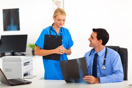 friendly male medical doctor talking to female nurse in office photo