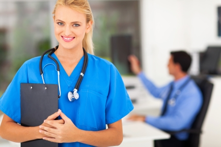 portrait of beautiful young nurse with stethoscope in doctors office photo