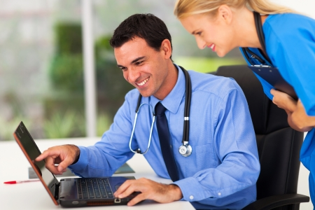 happy male doctor and medical assistant looking at computer