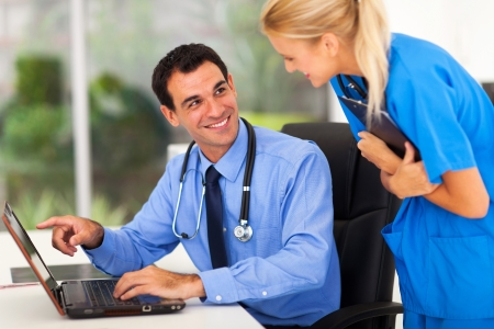 medical computer: cheerful male doctror discussing work with assistant in office