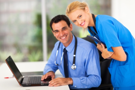 nurse clipboard: happy medical nurse and doctor smiling in office