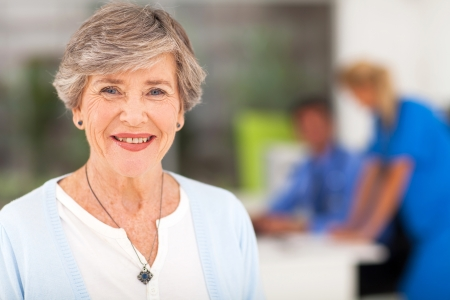 modern doctor: portrait of smiling senior woman in doctors office