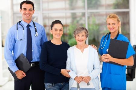 visits: retrato de los trabajadores de salud de pie con el paciente mayor y su hija