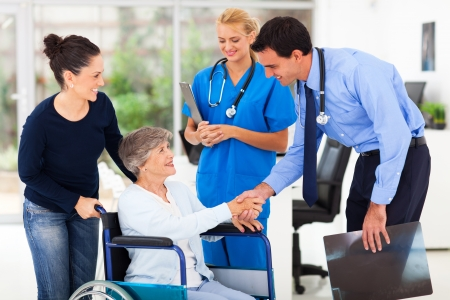 family doctor: friendly male medical doctor greeting senior patient  Stock Photo