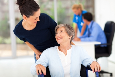 health care worker: loving adult daughter accompanying senior mother to visit doctor Stock Photo