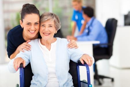 persona en silla de ruedas: cuidado hija adulta que acompaña a médico senior visitando madre