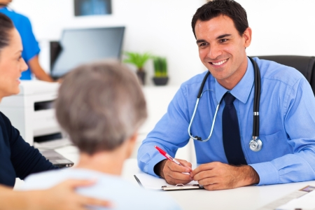 medical doctor consulting senior patient in office photo