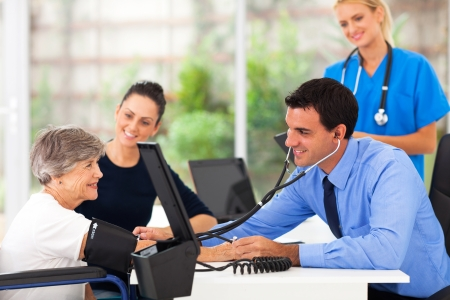 friendly medical doctor taking senior womans blood pressure photo