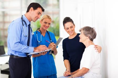 paciente: apuesto m�dico hombre escribe la prescripci�n m�dica de paciente mayor Foto de archivo